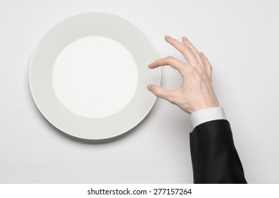 Business lunch and healthy food theme: man's hand in a black suit holding a white empty plate and shows finger gesture on an isolated white background in studio top view