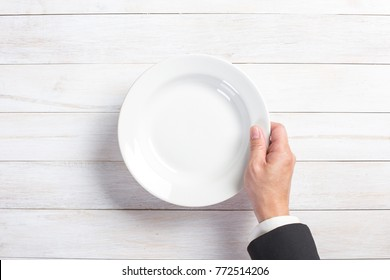 Business lunch and healthy food theme: man's hand holding a white empty plate