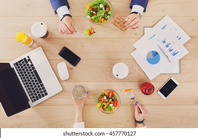 Business lunch together at working place. Businessman and woman's hands eating in office. Healthy diet food, vegetable salad with apple and juice. Cell phone, laptop and papers. Top view, flat lay
