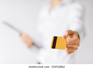 business, luxury, shopping and money concept - woman showing gold credit card