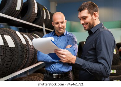 business, maintenance and people concept - male customer choosing wheel discs and salesman with clipboard at car repair service or auto store