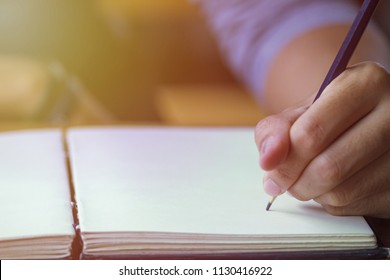 Business male hands with pencil writing on paper notebook.