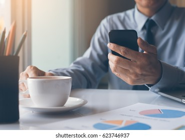 Business man or accountant holding mobile smart phone and working on laptop computer with business document, graph diagram and calculator, business strategy analysis, start up business concept
