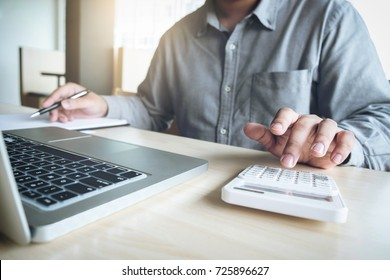 Business man or accountant working Financial investment on calculator with calculate Analyze business and market growth on financial document data graph and smart phone,Accounting,Economic,commercial.