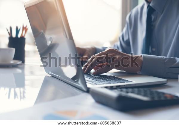 オフィスのテーブルにビジネスドキュメント、グラフ図、計算ツールを含むノートパソコンで作業するビジネスマンまたは会計士