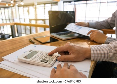Business man analysis data document with accountant calculating about fee tax at a office