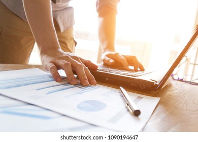 business man analyzing graph and chart document on office desk