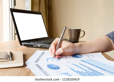 business man analyzing graph and chart document on office desk, home office concept