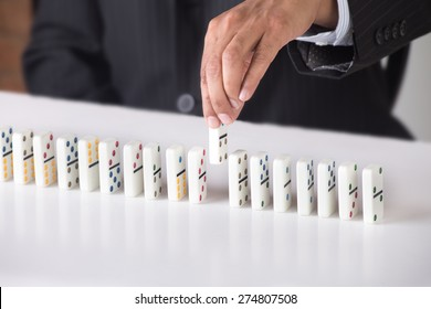 Business man is arranging dominoes in a line. Concept image for business strategy and game plan. Person is wearing a black suit and tie. He is seated in an office room with a white desk.