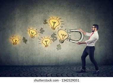 Business man attracts bright ideas light bulbs with a big magnet