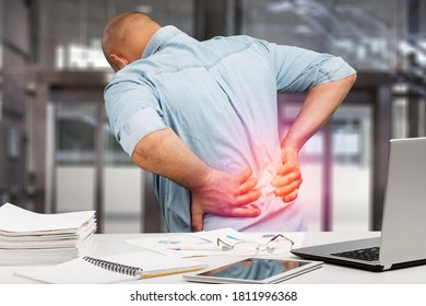 Business man with back pain in office