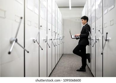 Business man, bank manager using notebook in a locker server room, safe deposit boxes with vault door.