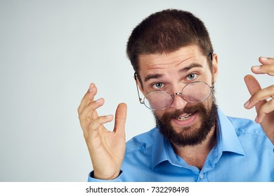 business man with a beard in glasses looks at the camera on a light background portrait