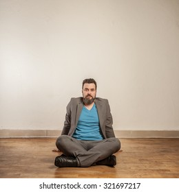 Business man with beard, sitting on wooden floor