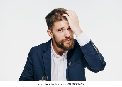 Business man with beard straightens hair on light background portrait