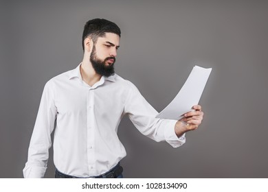 Business man with beard in white shirt holding documents on gray background.