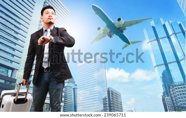 business man and belonging luggage watching to sky and hand watch against high building skyscrapers and passenger plane flying above use for aircraft ,air transportation ,traveling of people theme