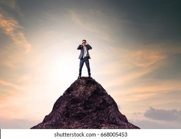 business man and binocular lens standing on top of mountain and looking through for searching something