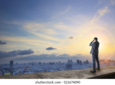 business man and binocular spying on top of building  with urban scene