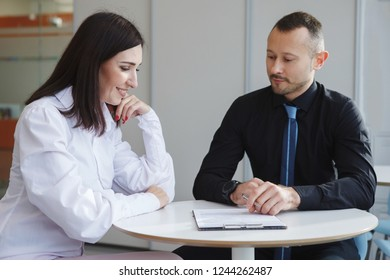 Business man in a black shirt and a woman in a white blouse are sitting at a table in the office and conclude a mutually beneficial contract. Good deal. Favorable agreement.