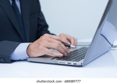 Business man in black suit holding a pen and working, typing on laptop computer keyboard in office room, close up, online working concept, internet of things.