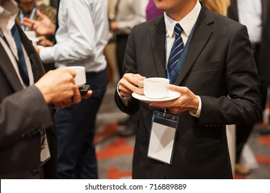 Business man with black suit holding a white cup of coffee or tea while having conversation with his friend and the hi-tea event.