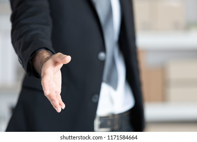 Business man  in black suit  open hand ready to shake hands, partner shaking hands, shaking hands, focus on hand.