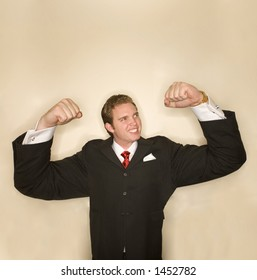 Business man in black suit, red tie, and white shirt is flexing is arms in a pose of strength whose arms are incredibly exaggerated