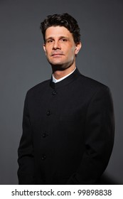 Business man with black suit and white shirt isolated on dark background. Studio shot.