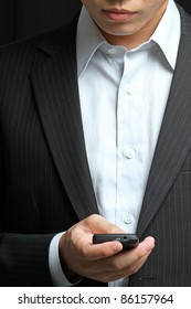 business man in black suit working on pda or smartphone