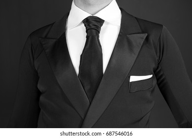 business Man in a black tuxedo suit and white shirt and black tie on a black background. Without a face. The businessman in the dark. Studio shot