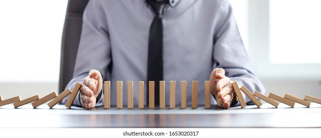 business man blocks falling blocks with his hands to prevent domino effect