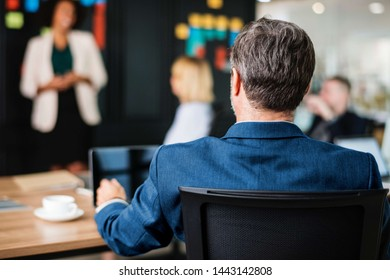 Business man in blue jacket suit at a desk conducting meeting with staff.