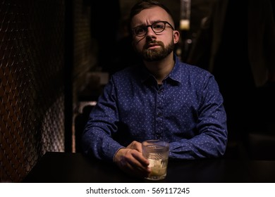 Business man, in blue shirt and glasses, drinking cocktail of vintage old fashion glass in loft bar