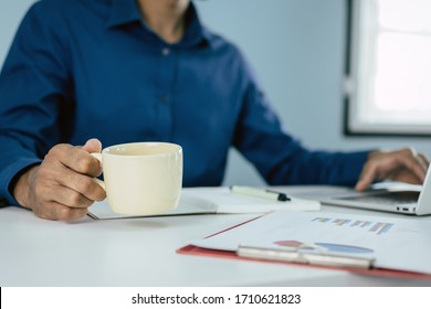 business man in blue shirt holding coffee cup and working with computer and document report on desk at home, self quarantine, work from home, marketing, business finance, digital technology concept