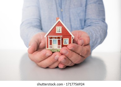 Business man with blue shirt are holding hands over red miniature house to illustrate the importance of insurance and security.