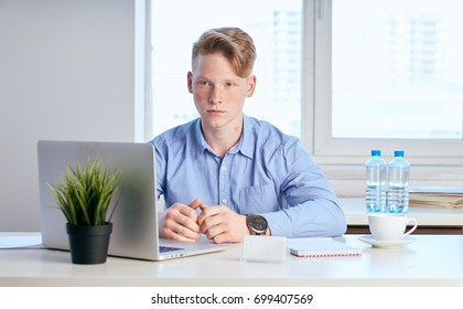 Business man in blue shirt is sitting at office desk in office