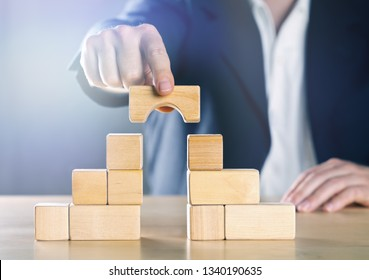 Business man bridging the gap between two towers or parties made from wooden blocks; conflict management or mediator concept, blue toned with ligth flare
