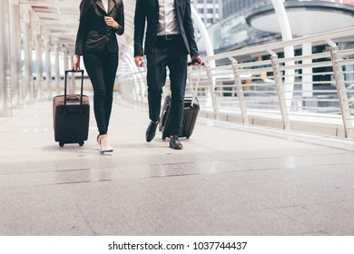business man and businesswoman wear black suit walk together with luggage on the public street, business travel concept