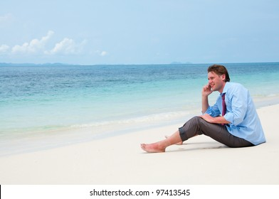 Business man calling by cell phone on the beach