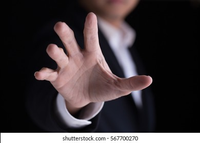 A business man in casual black suit gesturing  his palm hand against the camera.