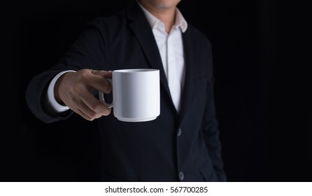 A business man in casual black suit holding a cup of coffee.