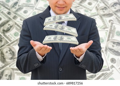 Business man catches falling money with money background