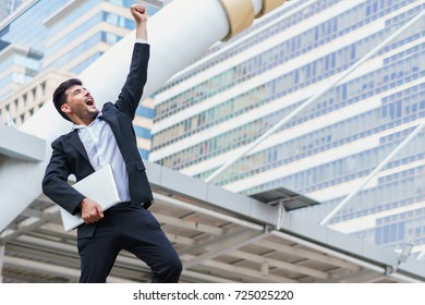 Business man celebrating success. Young businessman show arm raised and hold laptop computer while standing outdoors with office building in the background.