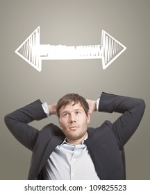 Business man in chair thinking with arrows in different directions over his head