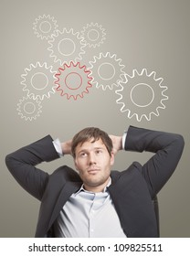 Business man in chair thinking cogwheels over his head