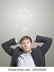 Business man in chair thinking with a light bulb over his head