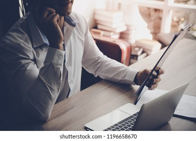 Business man is checking out marketing report and call partner