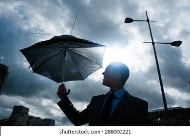 Business Man in the City with umbrella on stormy day