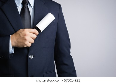 Business man cleaning his suit with adhesive lint roller on white background